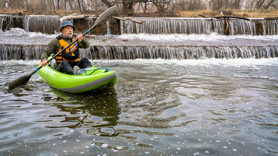 Senior man riding an inflatable kayak